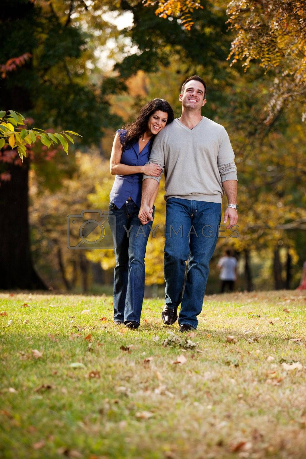 A happy couple walking in the park on grass