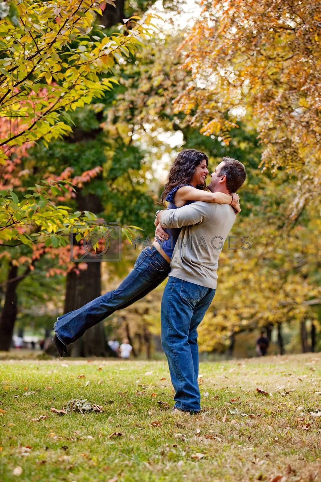 A man and woman hugging in a park
