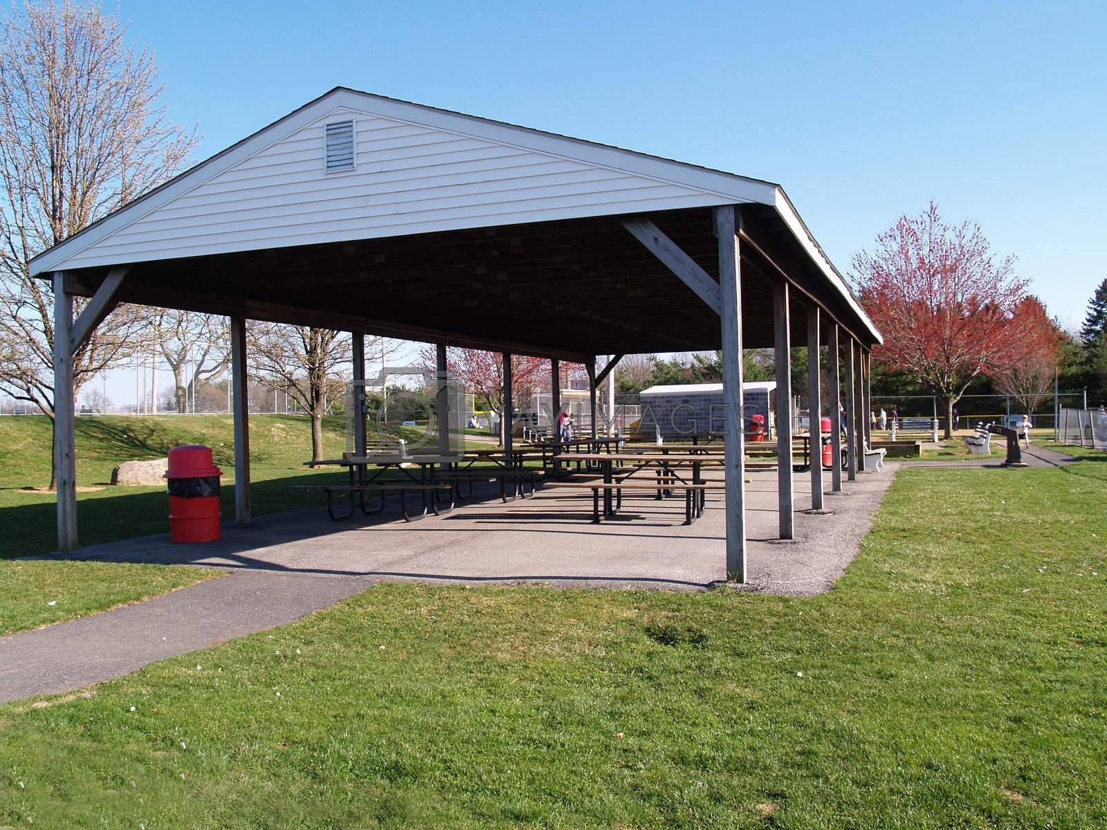 an empty outdoor picnic area with a covered roof and tables