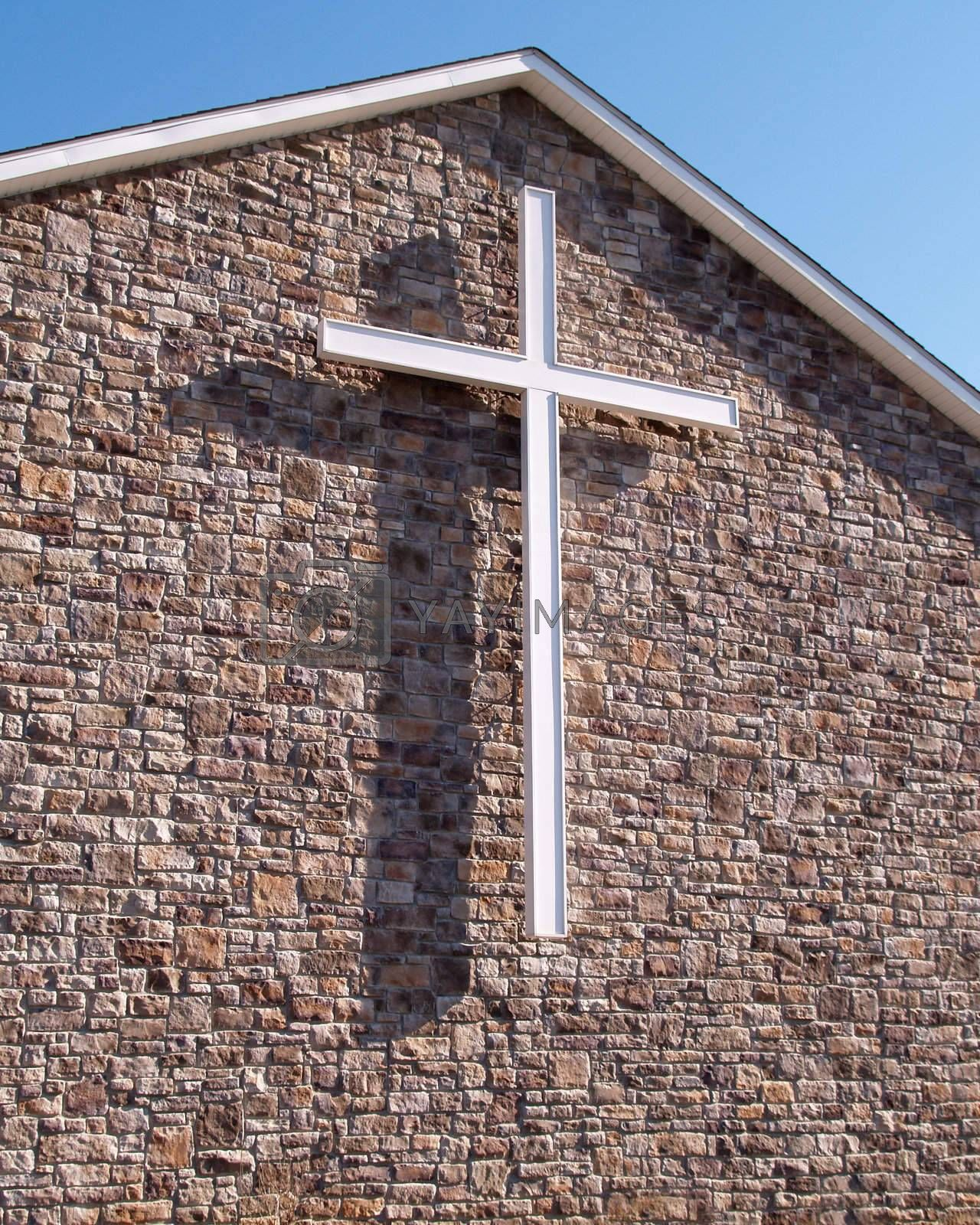 a white cross on the exterior of a modern stone church