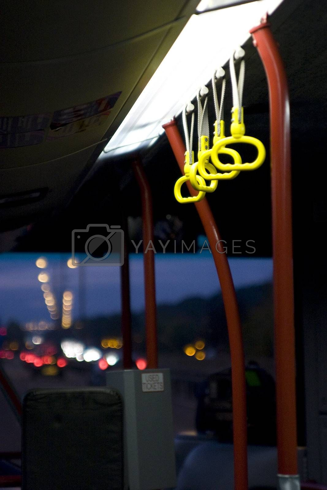 Bus interior showing handles and the road ahead from the perspective of a traveller
