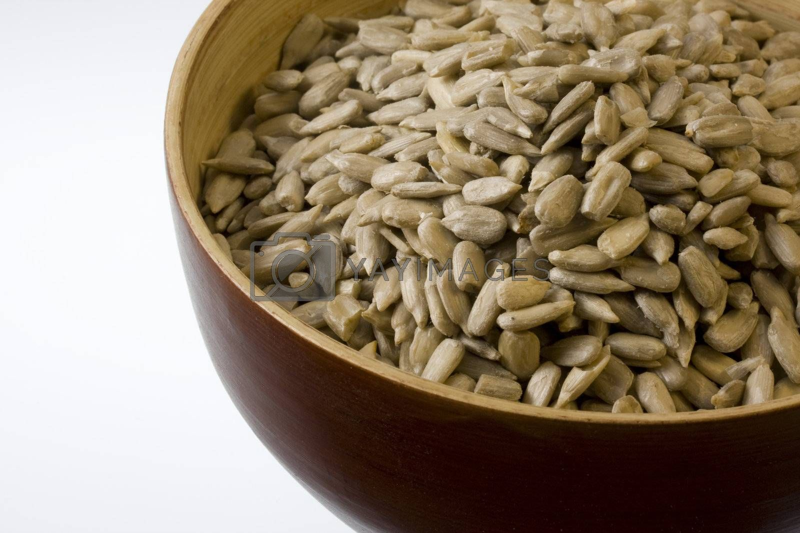 a wooden bowl of shelled sunflower seeds against white background, copy space