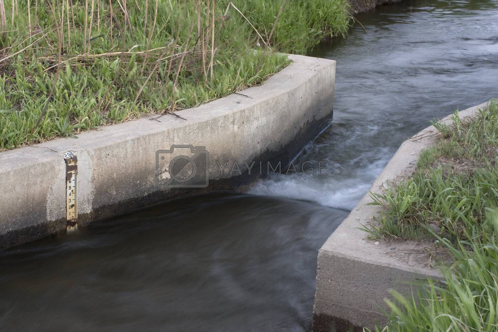 irrigation ditch with a flow measurement concrete structure and water scale, Colorado