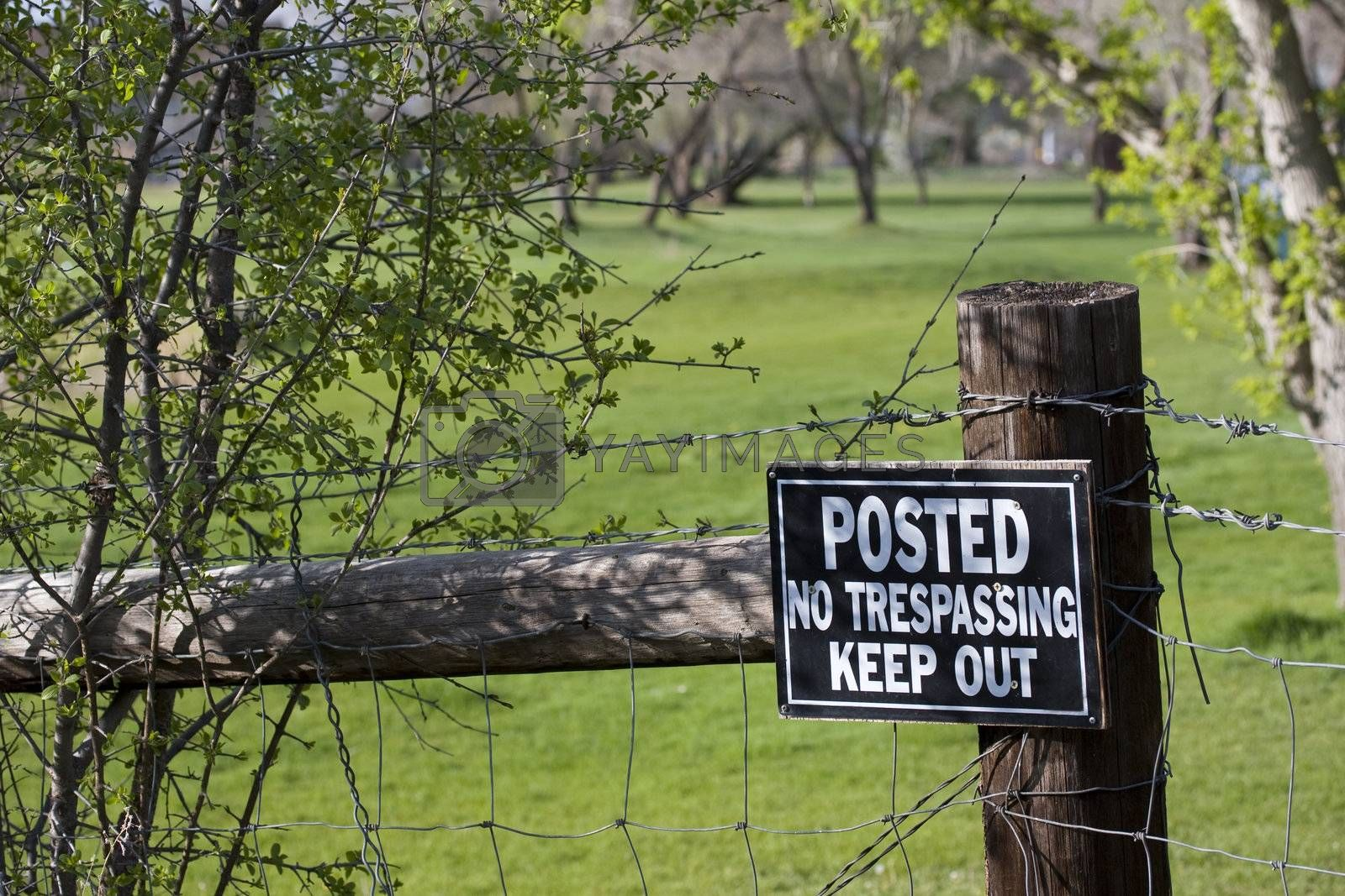 no trespassing - keep out sign on a fence surrounding green meadow or golf course