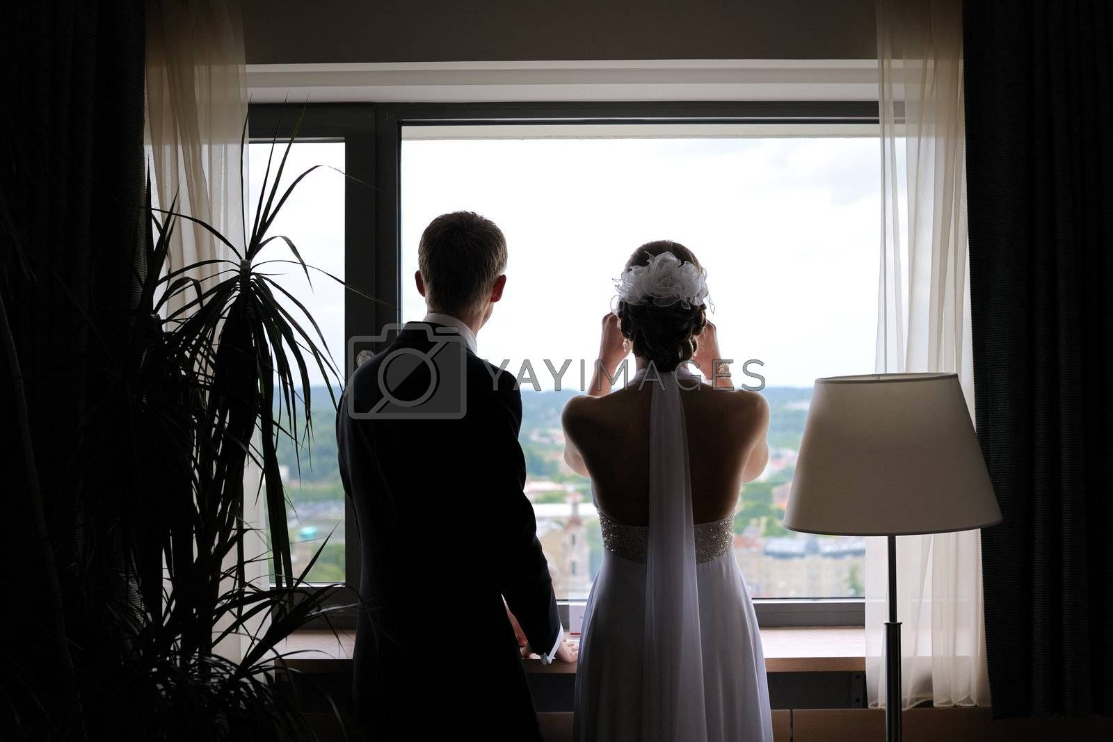Bride and groom are standing agains the window looking at the city