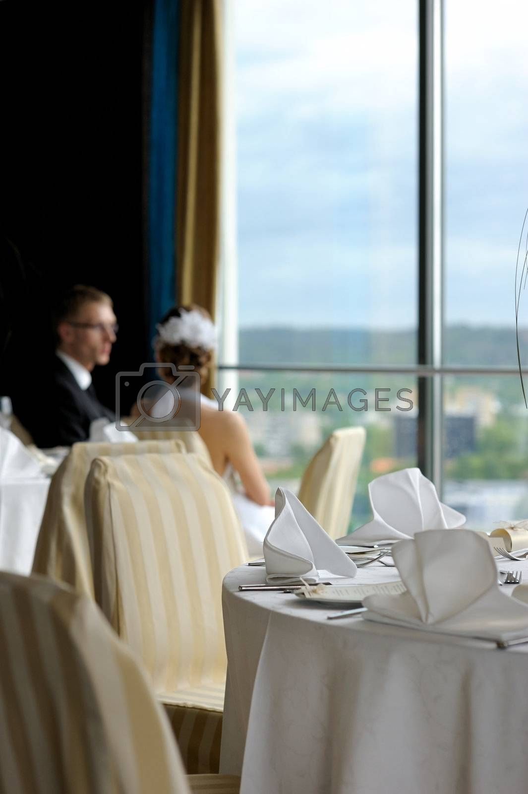 Groom and bride in the cafe looking at the city through the window
