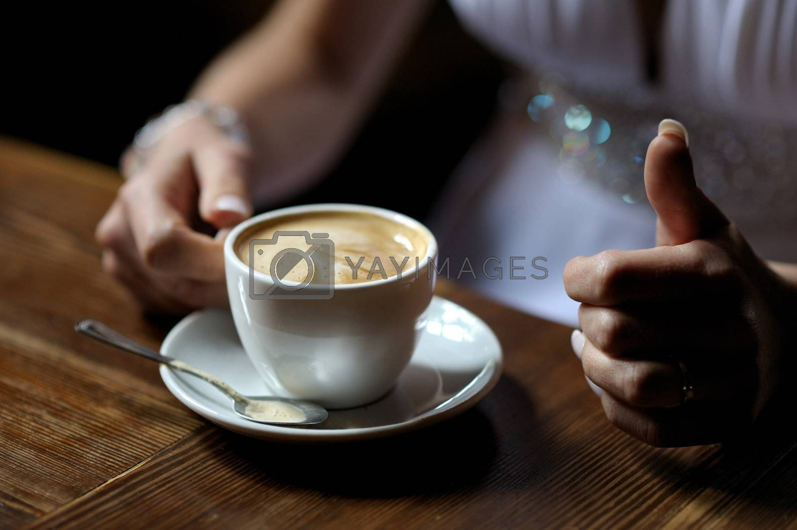 Bride's hands holding cup of coffee close-up