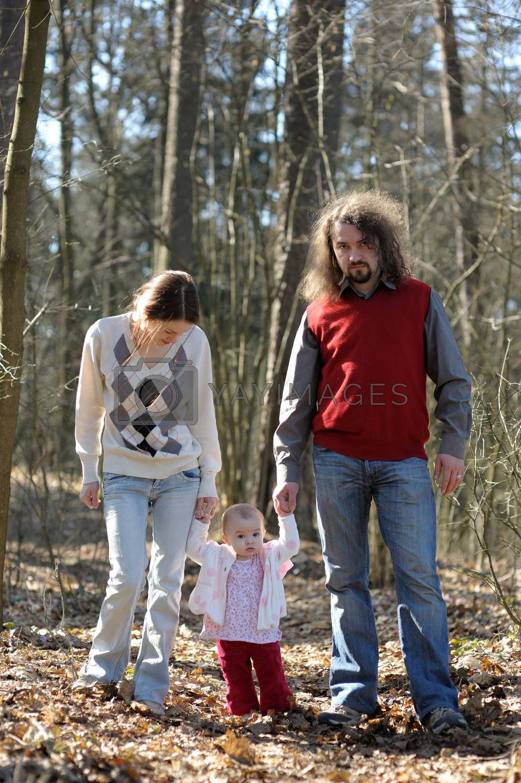 Young couple with their baby walking in the forest