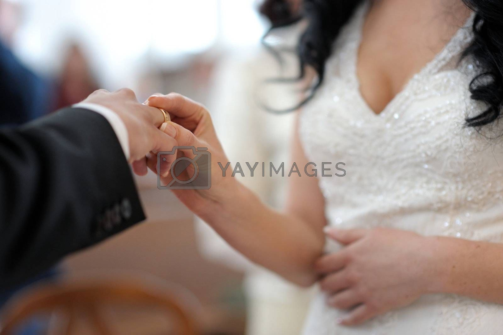 Bride is putting the ring on groom's finger