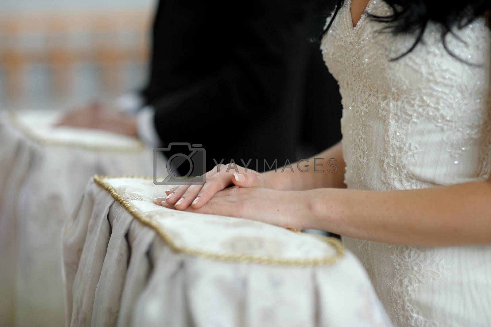 Bride's hands on the pillow close-up during wedding church ceremony
