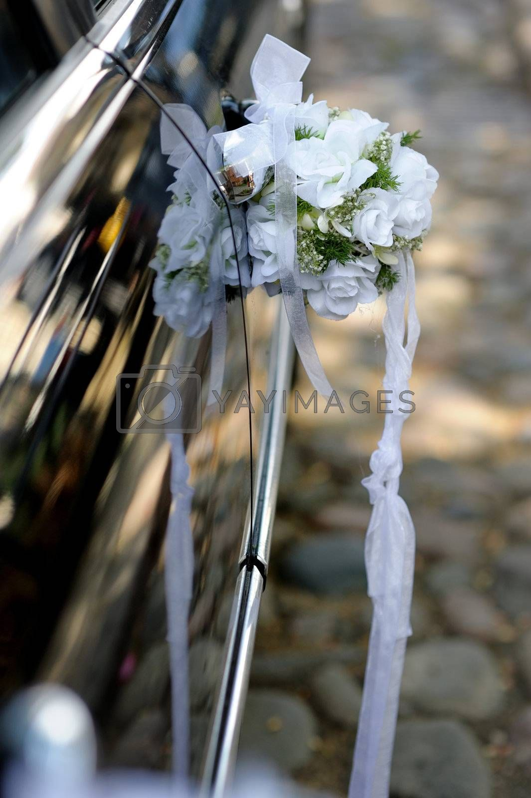 Floral decoration made of white roses on the black car door