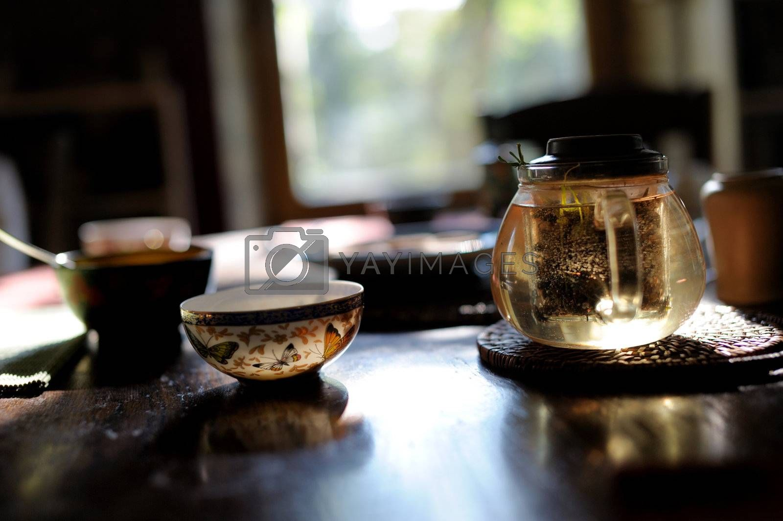 China tea cups and glass teapot on the table in the sunlight against the window