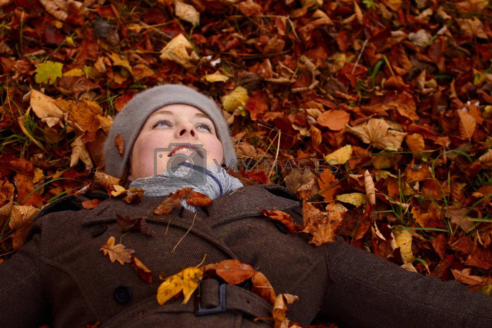 Royalty free image of Fall - young woman lying down in leaves by FreedomImage