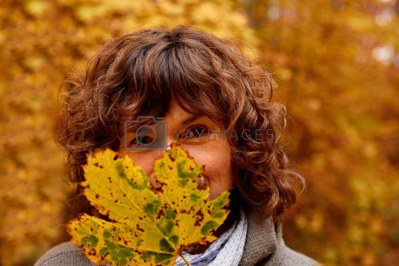 Royalty free image of Mature woman hiding behind a  maple leaf by FreedomImage