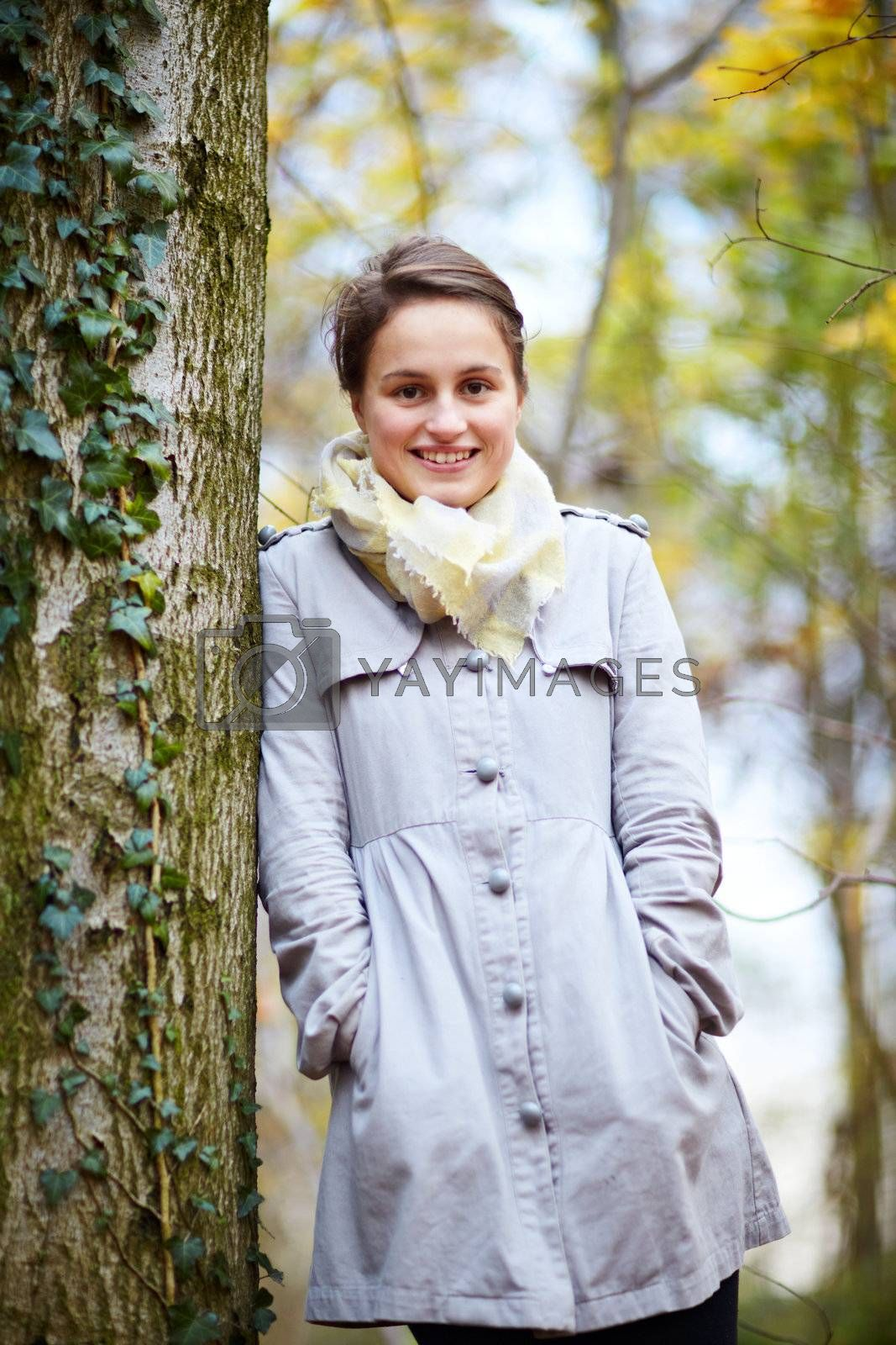 Royalty free image of Trendy young woman standing beside a tree by FreedomImage