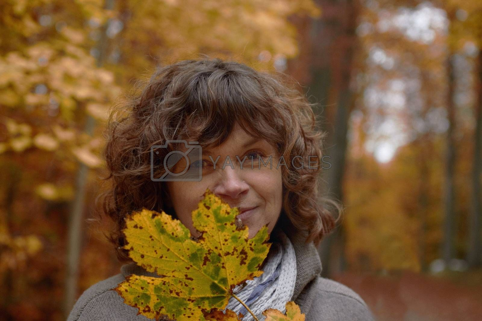 Royalty free image of Autumn - middle aged woman looking at you behind a maple leaf by FreedomImage