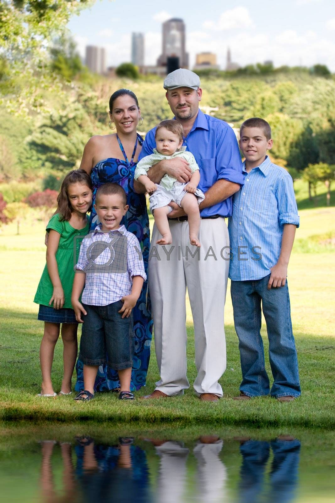 Portrait of an attractive young family with four children posing in a park outside of the city.