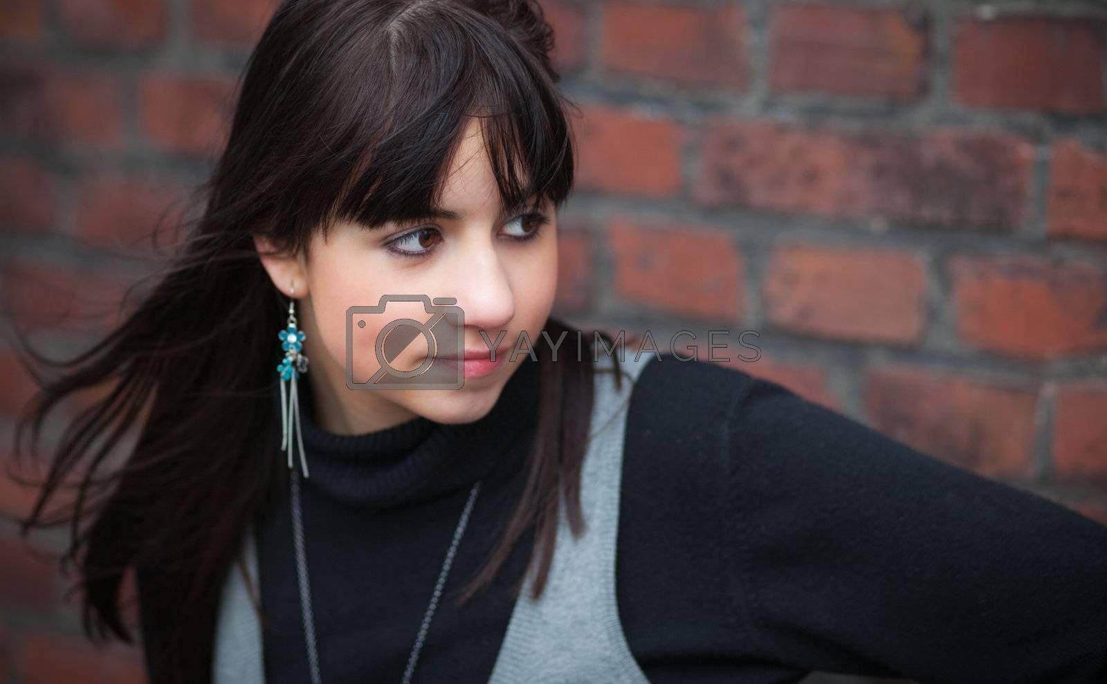 Pensive brunette girl against a red brick wall; blurred background
