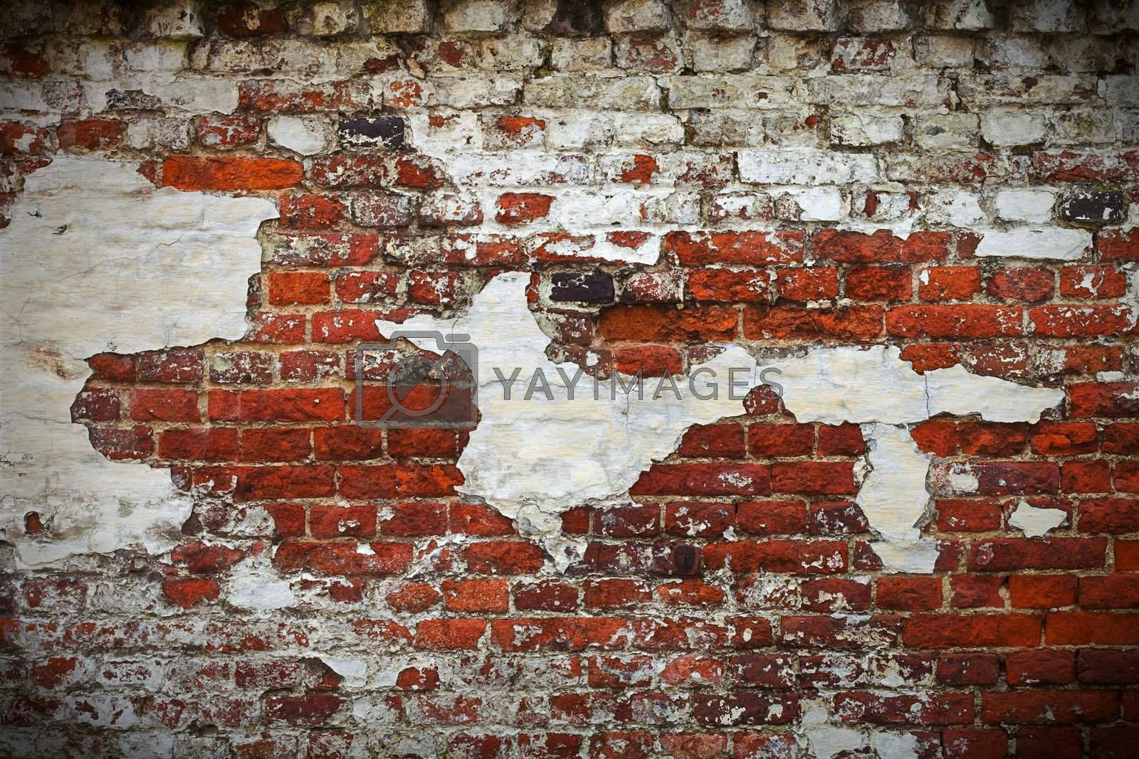 Grunge red brick wall texture with remaining plaster (stucco)