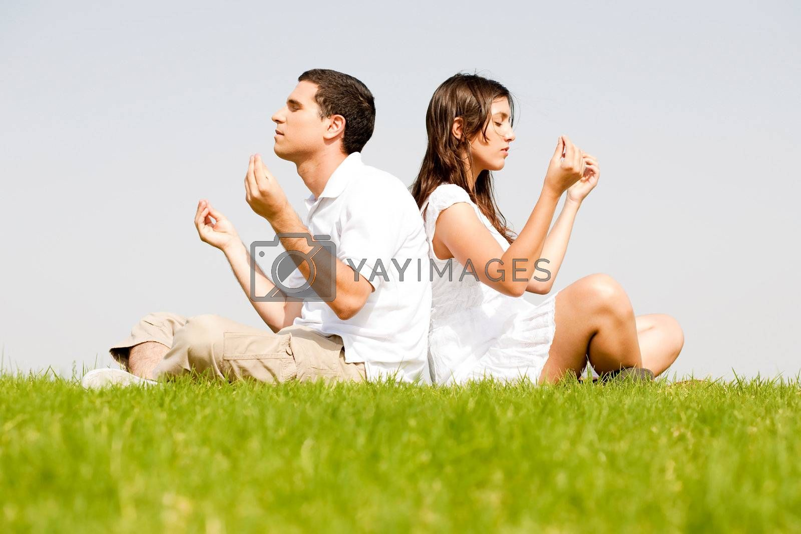 young couple sitting on grass and doing meditating