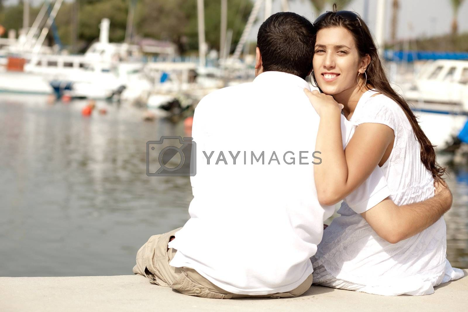 Young Couple Seated and Hugging On A Footbridge , Focus On Female
