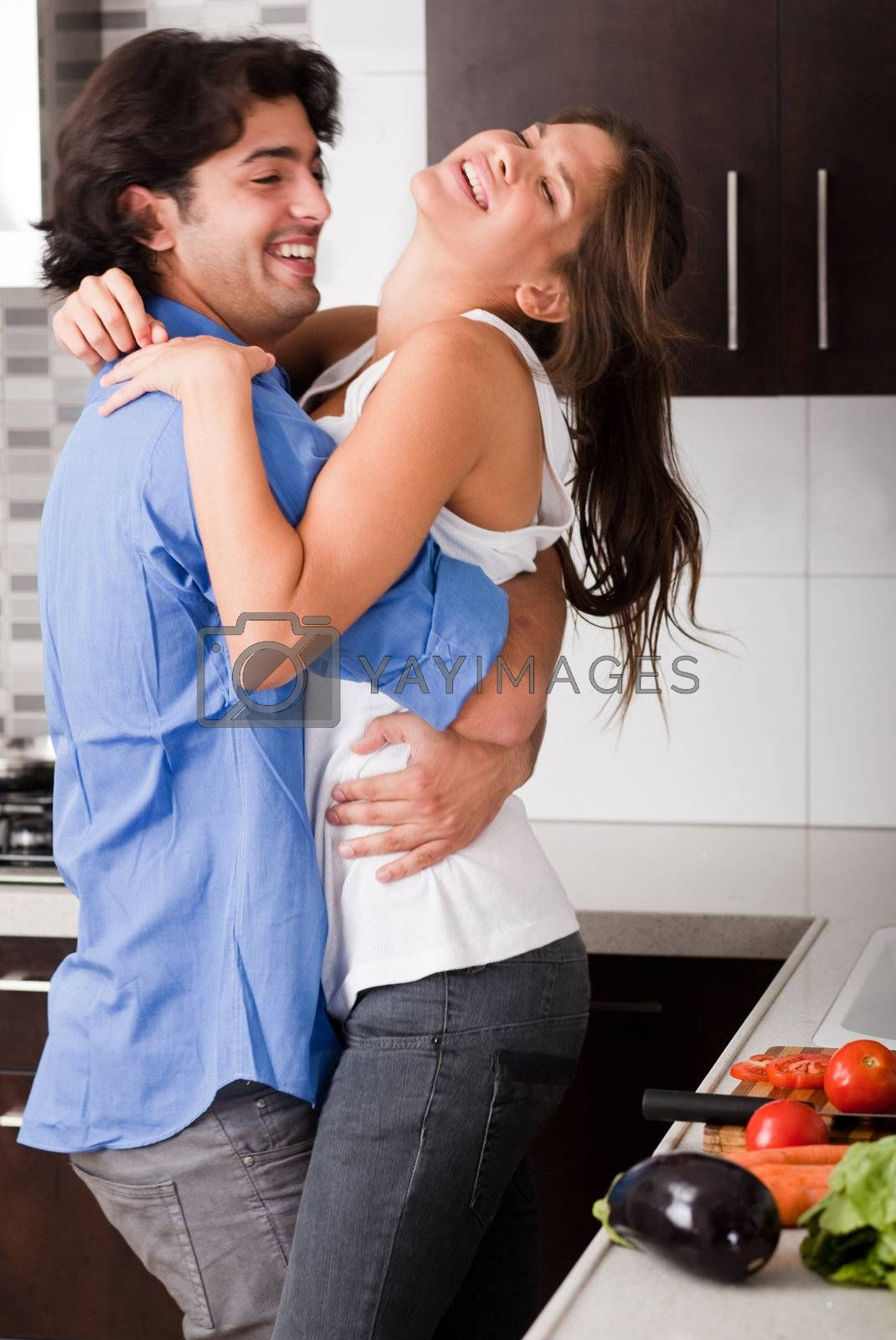 playful young couple enjoying their love in kitchen
