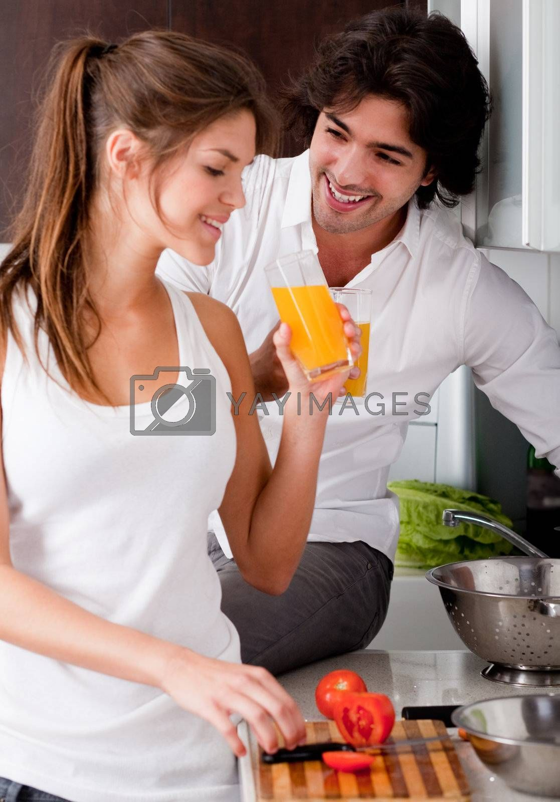 happy young couple in the kitchen and drink orange juice