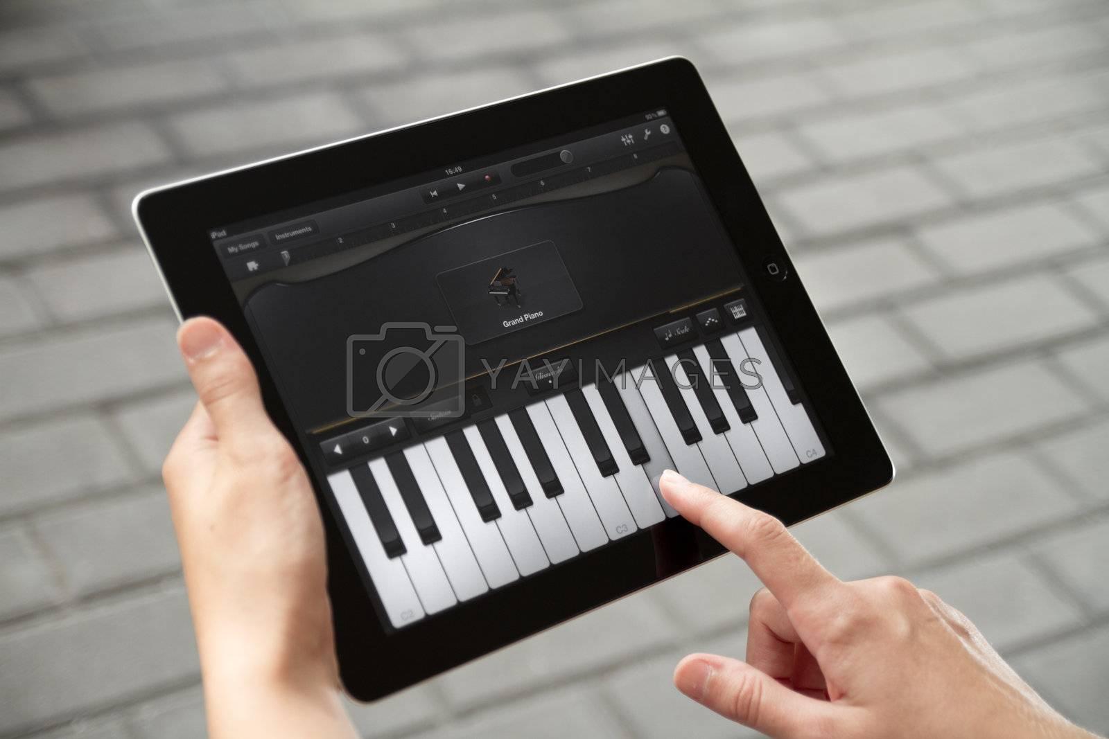 Play the piano at Apple Ipad2 by bloomua