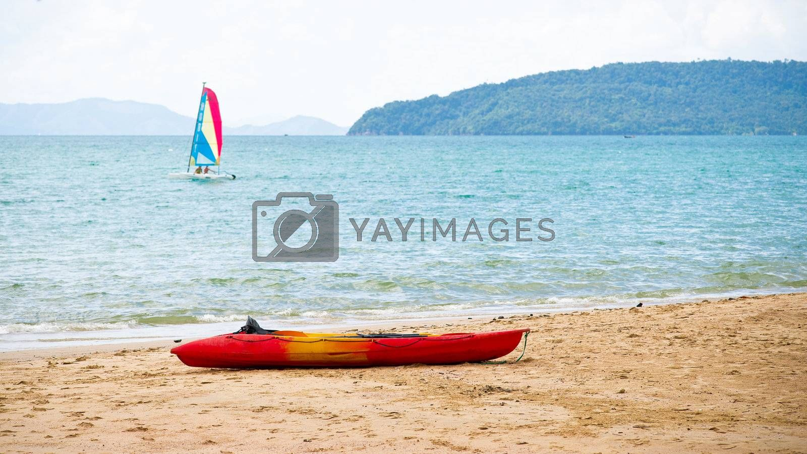 Sailing-boat in the sea and kayak on the beach
