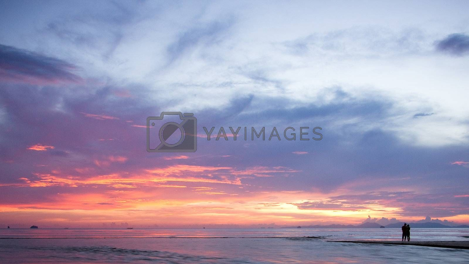 Silhouettes of romantic couple on a beach at sunset