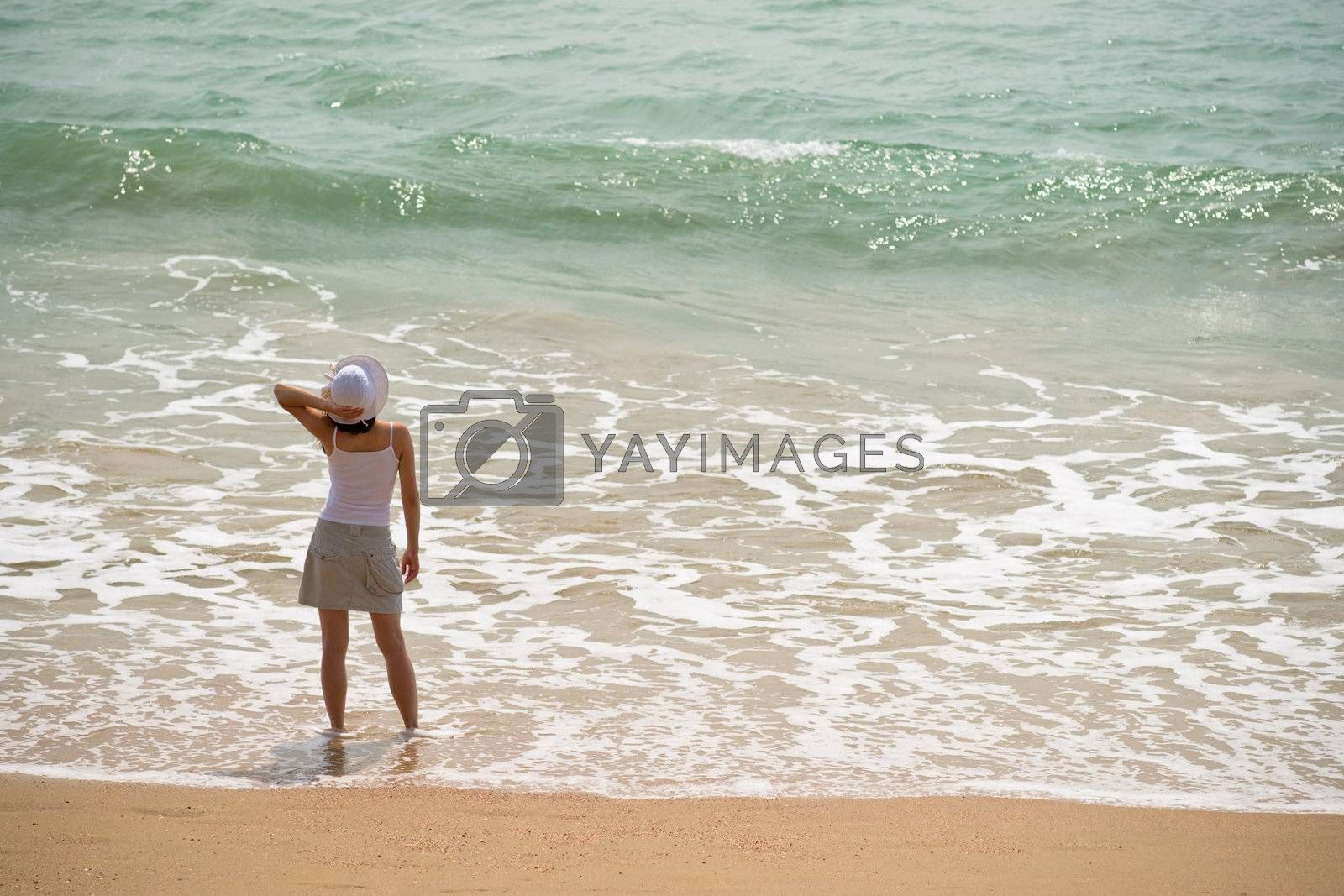 Woman standing in the sea waves