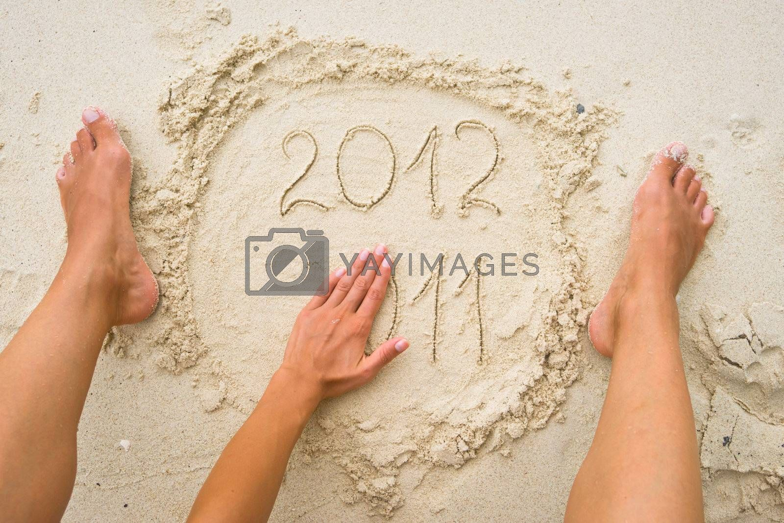 Female hand erasing numbers 2011 on the sand