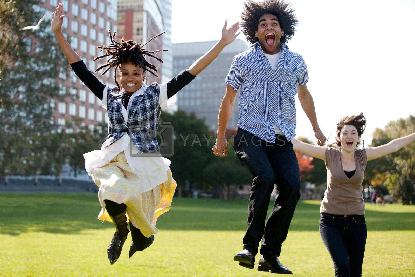 A group of people jumping for joy in a city park