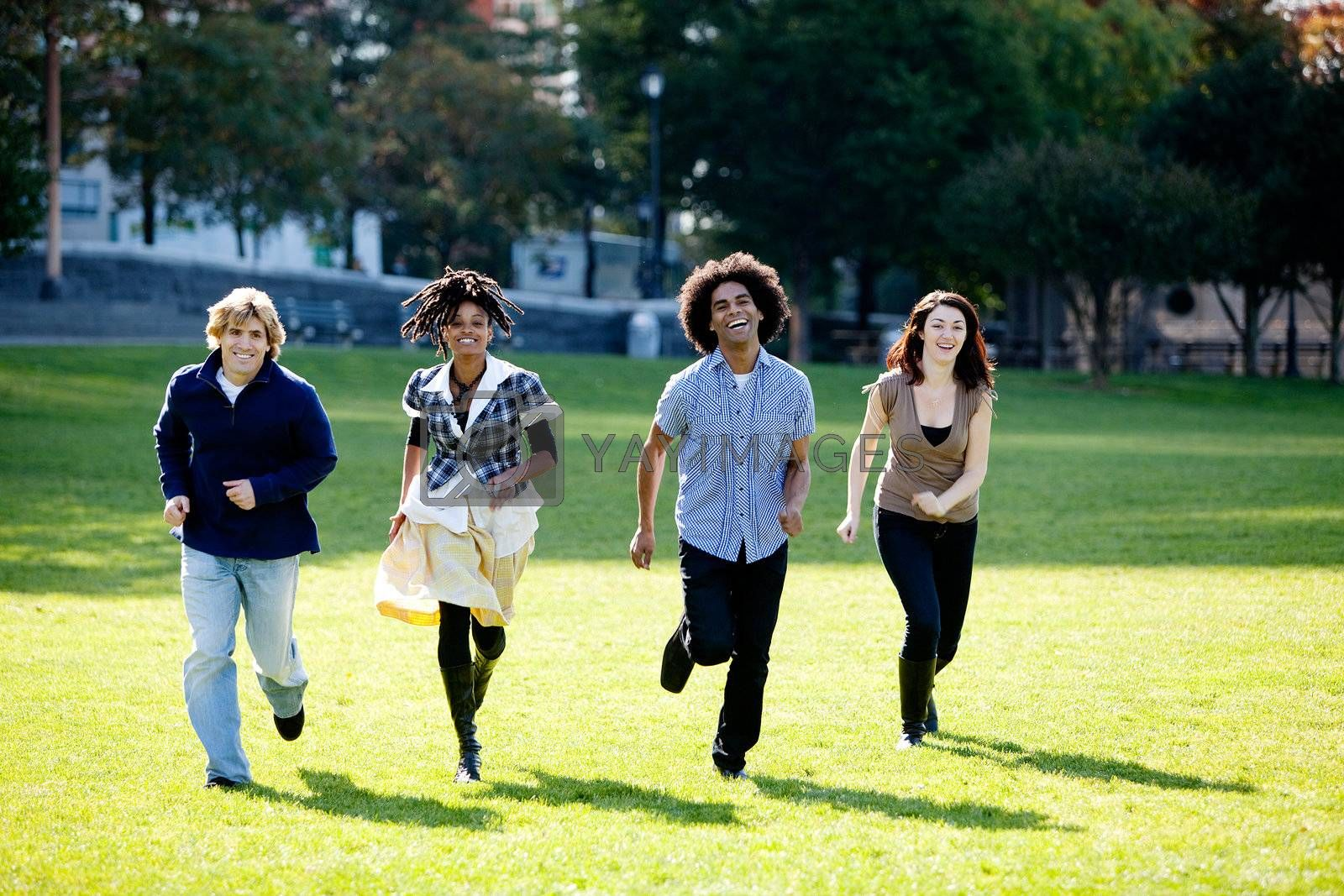 A group of people in a park, running towards the camera