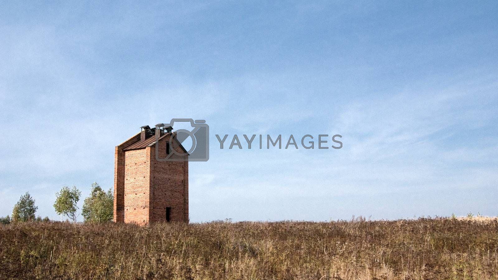Brick house in the field on the sky background