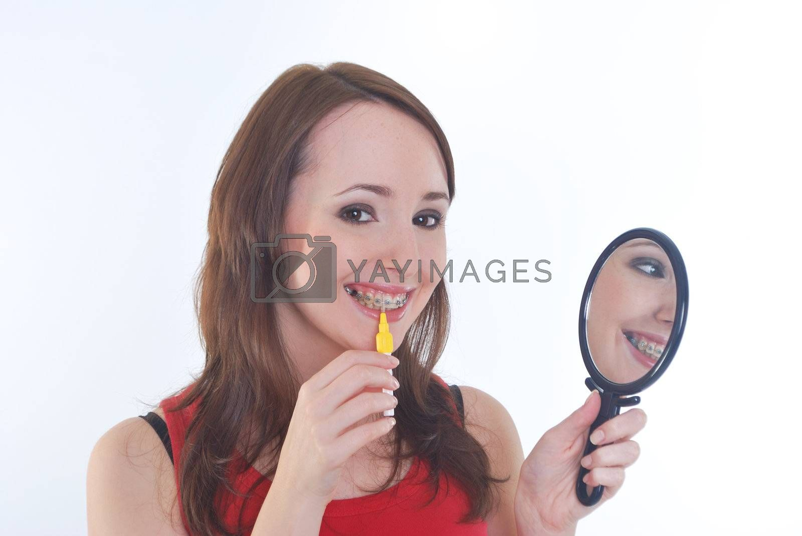 pretty girl with braces cleaning teeth