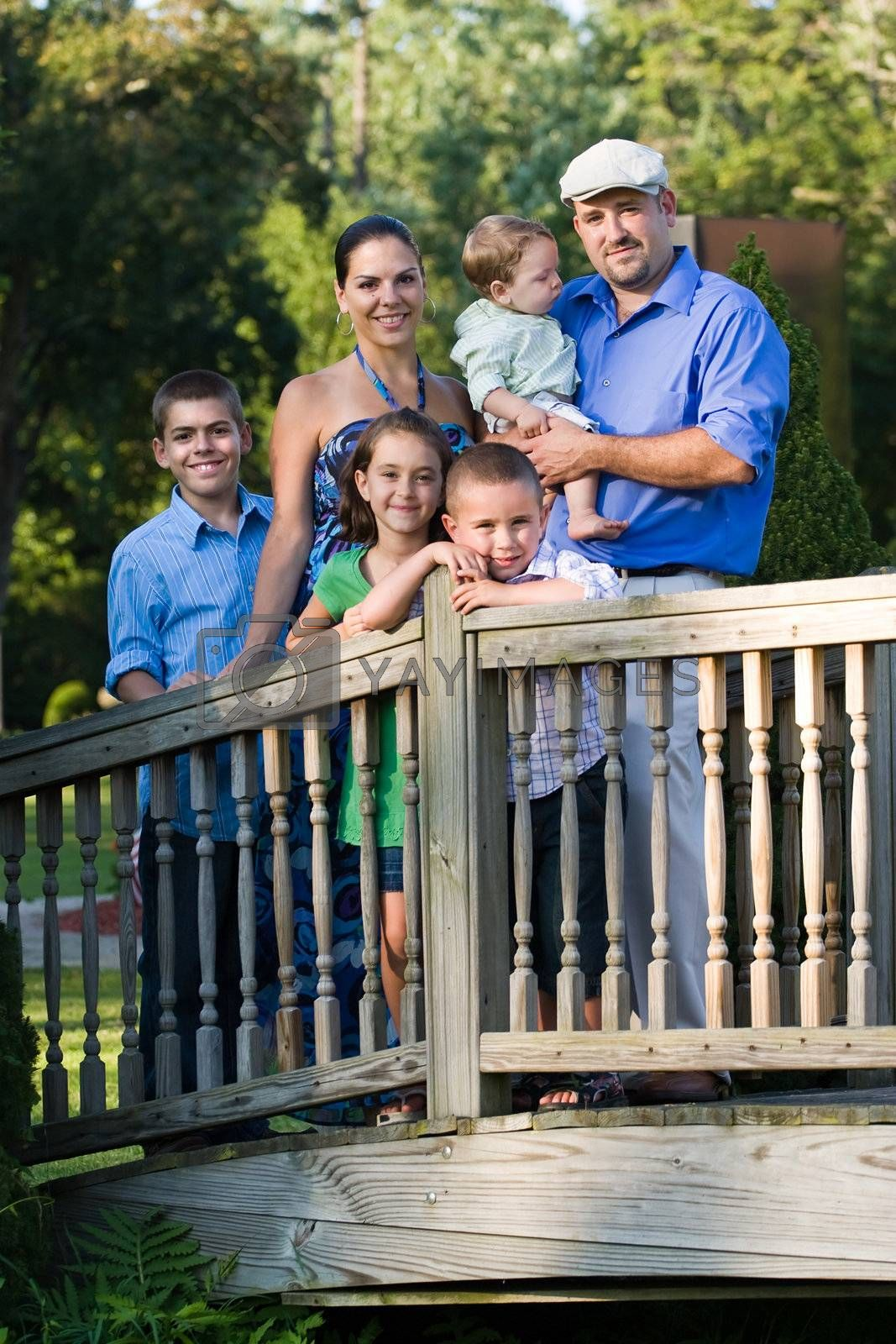 Portrait of an attractive young family with four children posing in a park on a wooden walking bridge.
