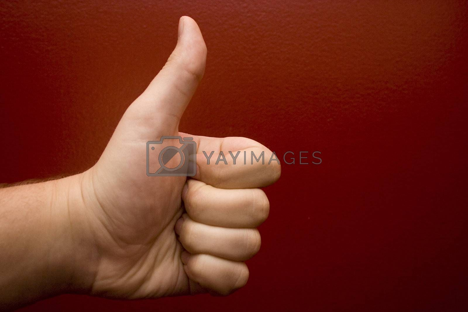A hand giving a thumbs up on a burgundy background