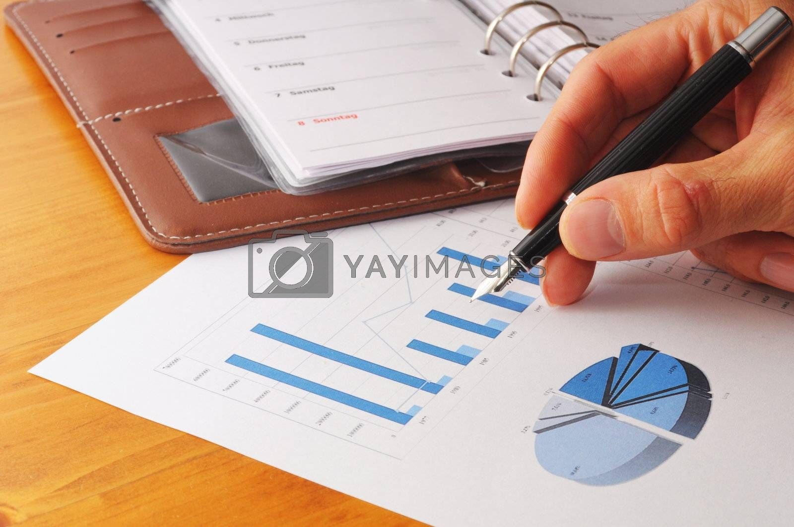 hand and paperwork with business information  and pen