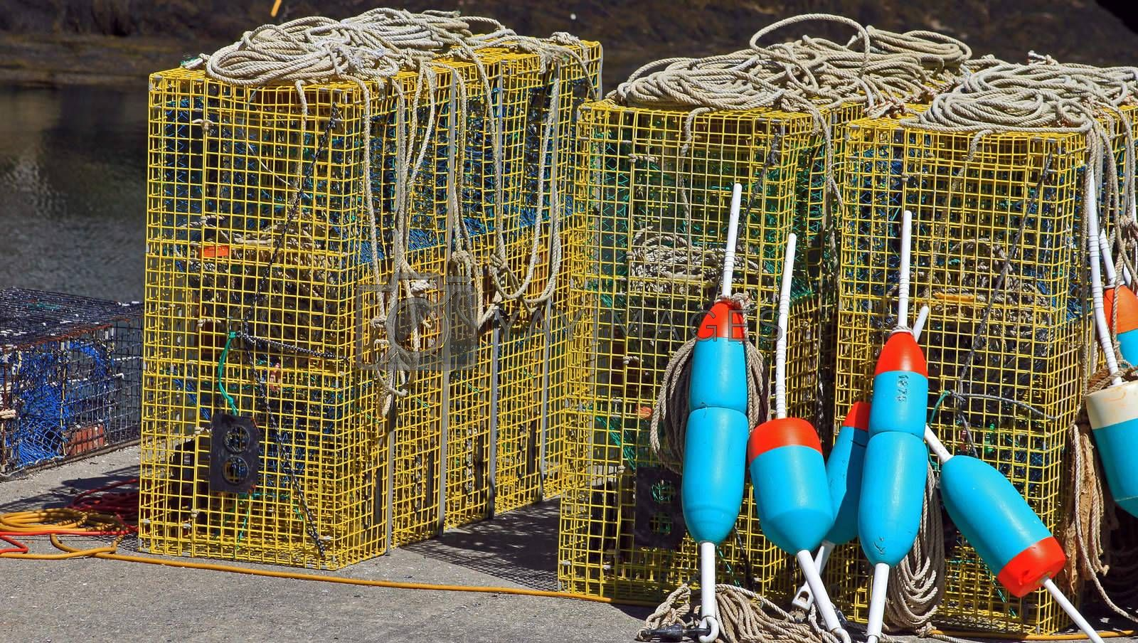 Lobster buoys leaning on cages on fishing wharf