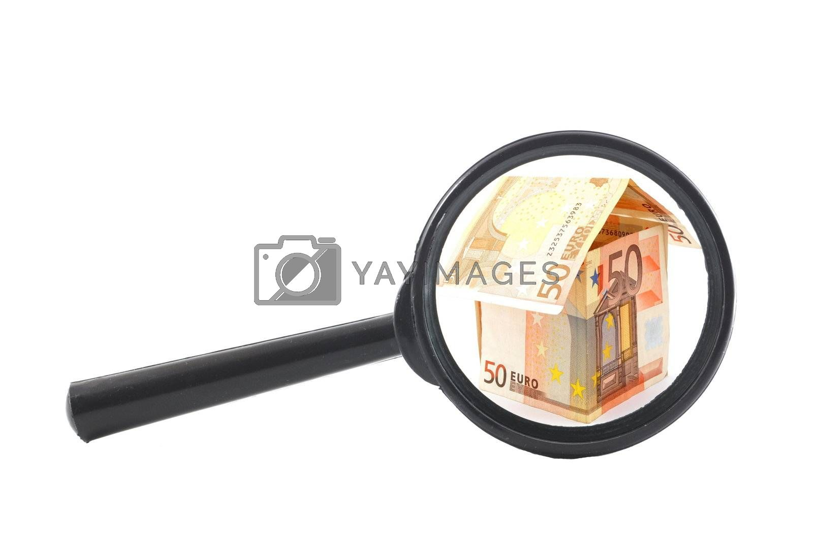 house of money and magnifying glass showing real estate concept