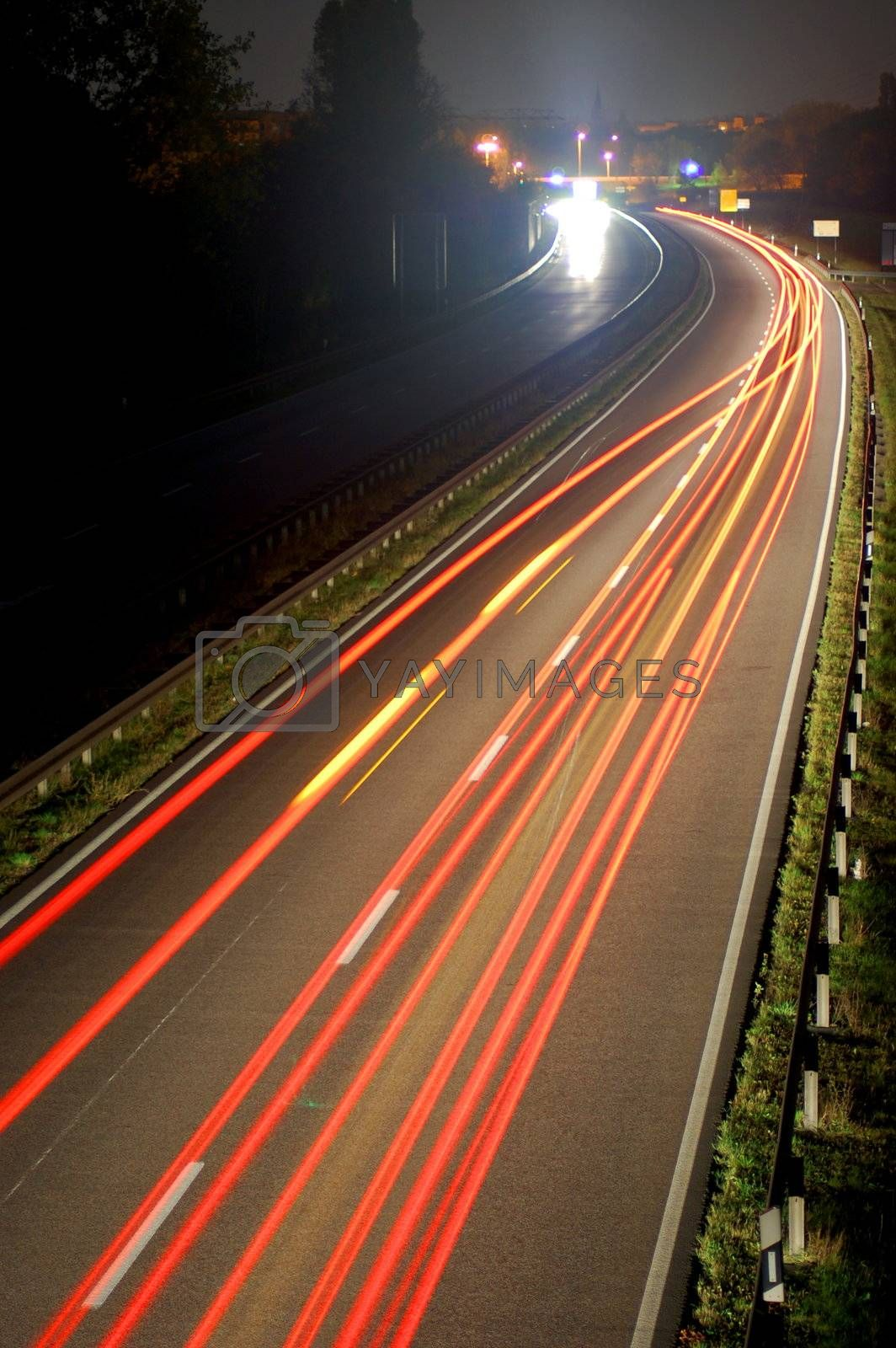 road with car traffic at night and blurry lights showing speed and motion