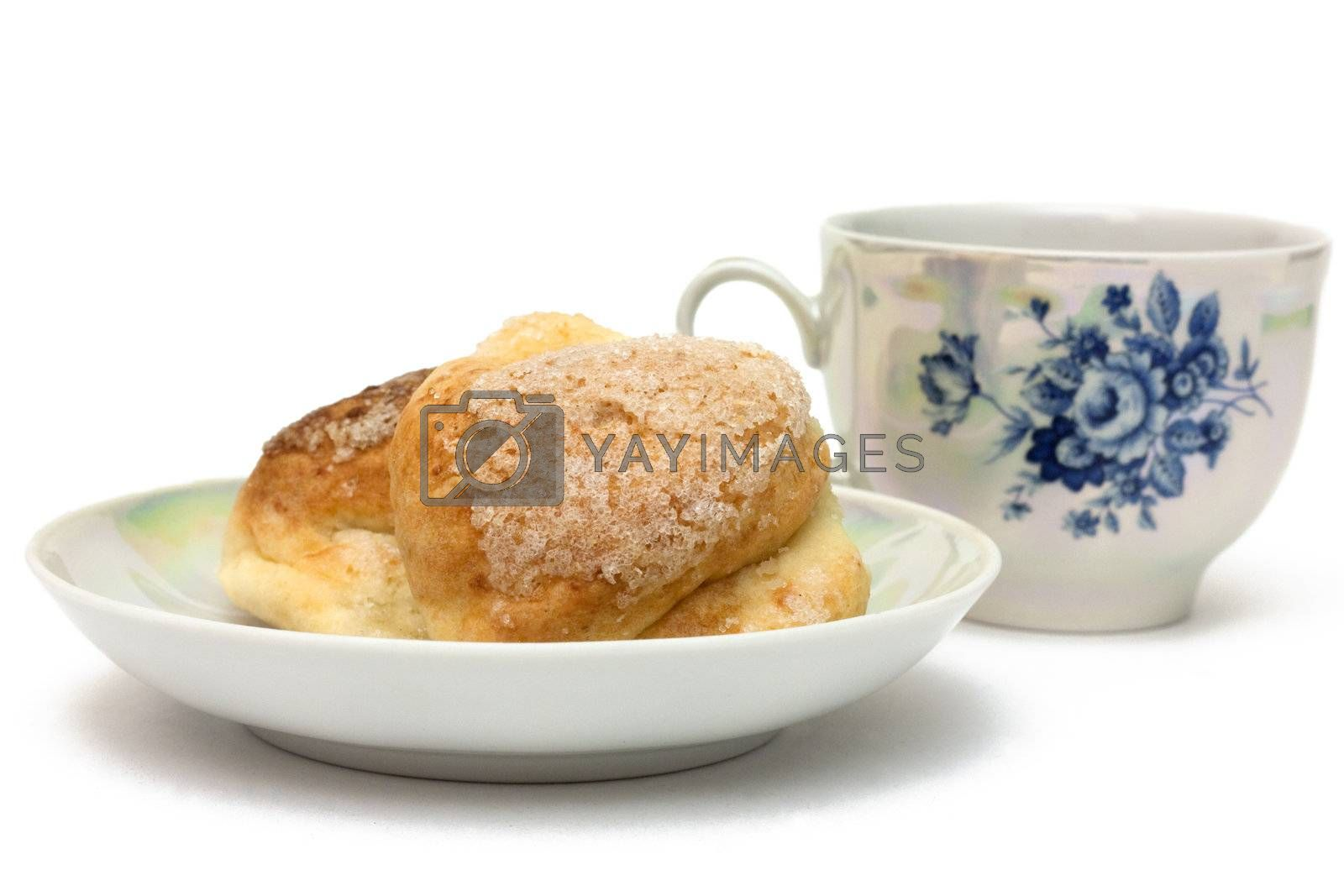 Baked goods on a saucer with a cup of tea isolated on white
