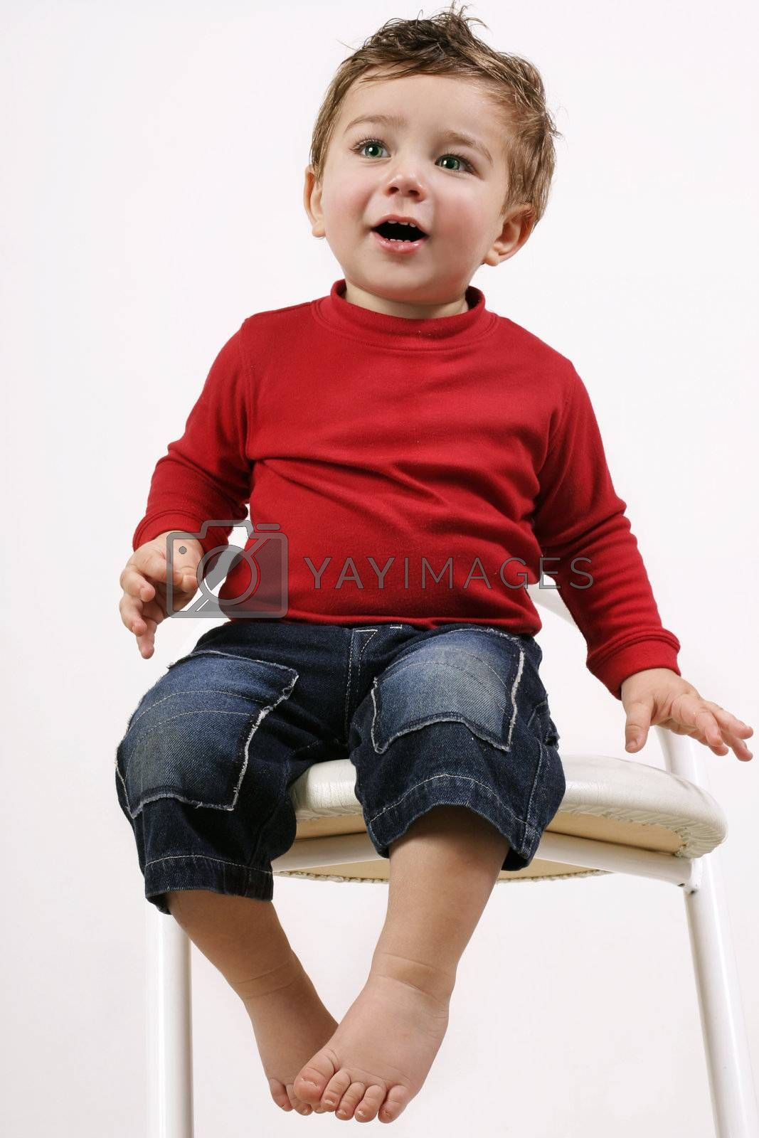 Adorable young toddler sitting on a white stool