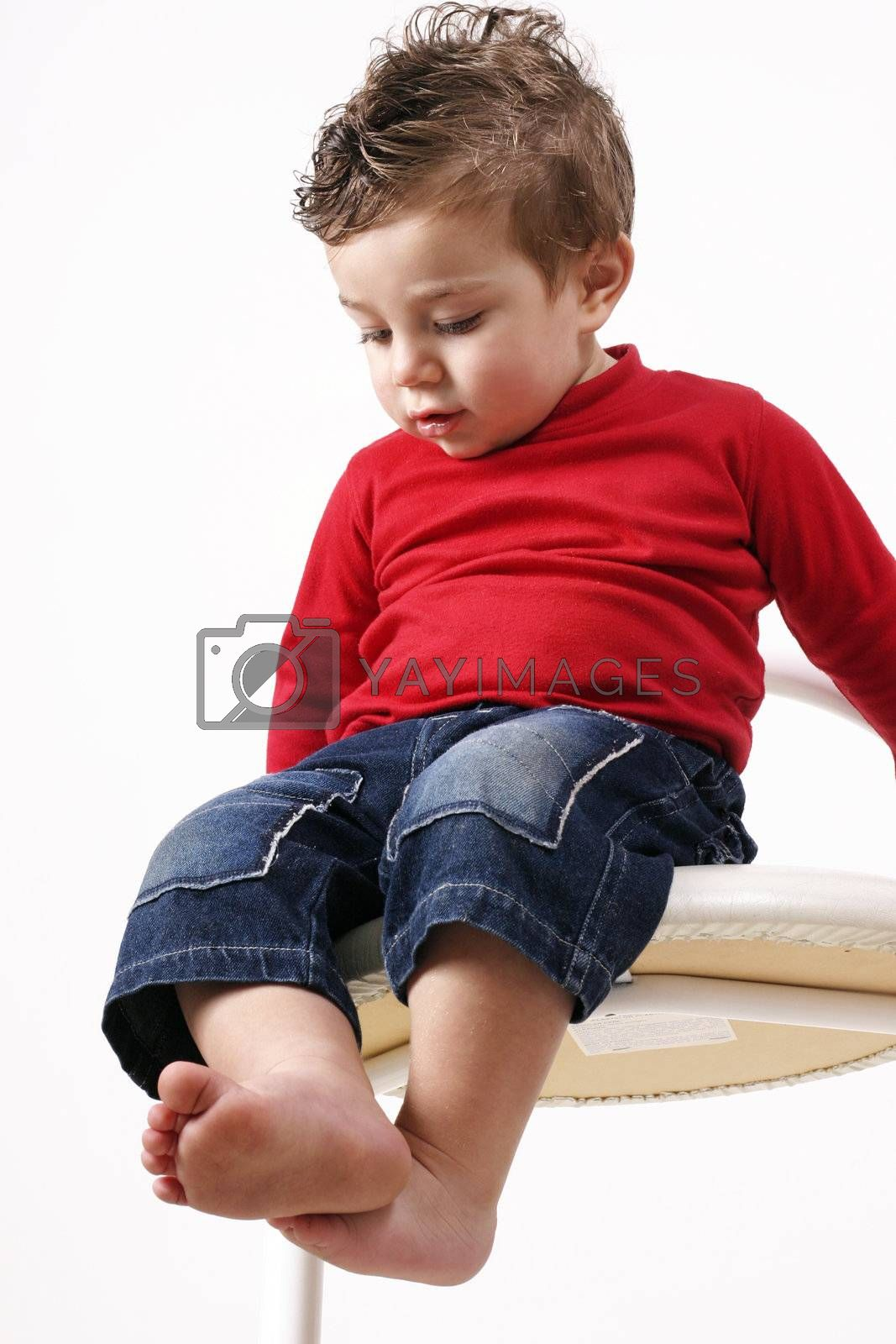 Toddler sitting  on a high stool makes an observation of his surroundings