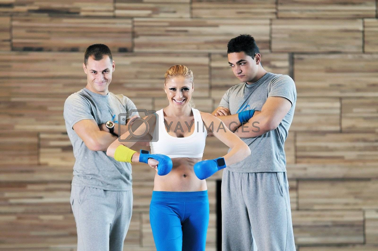 group of young adults exercise in fitness club with trainer