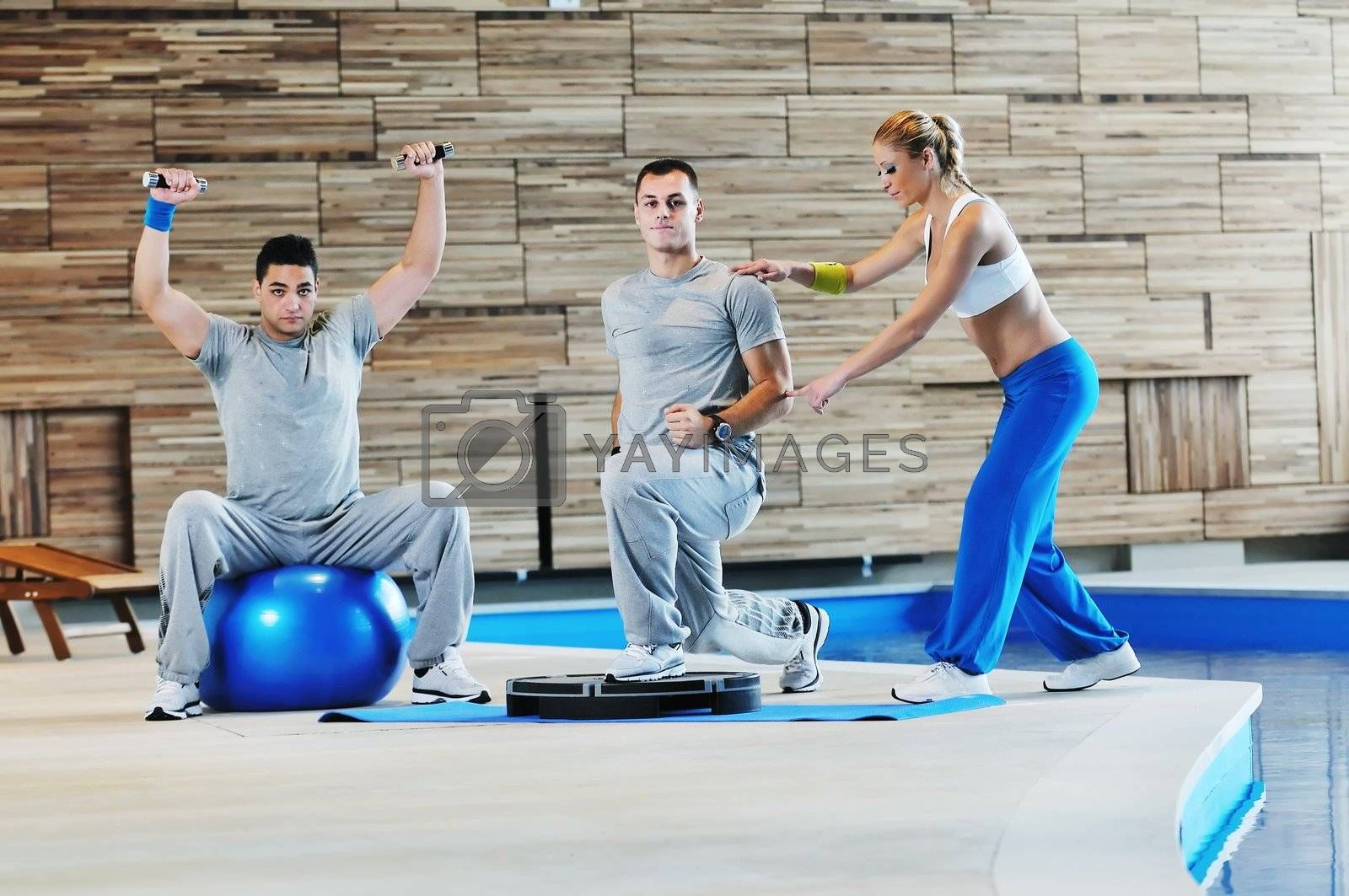 fitness personal trainer on fitness classes supporting group of people and wotrking out together in team