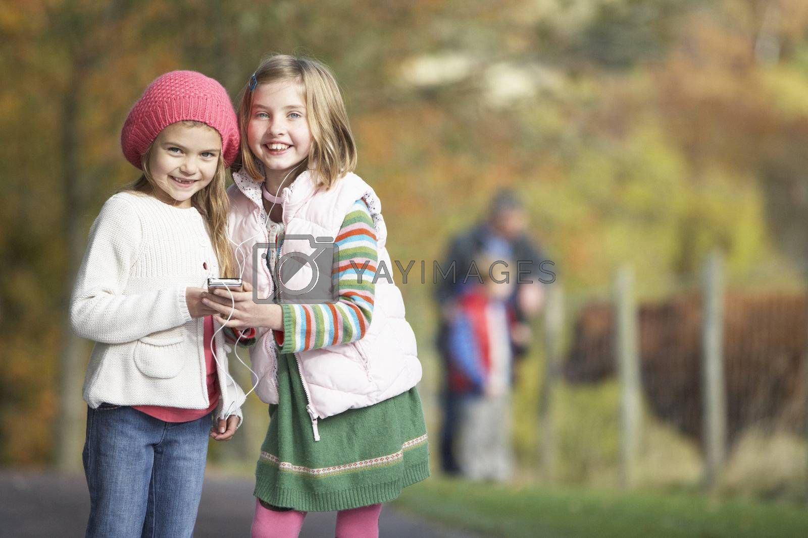 Two Young Girl Listening To MP3 Player Outdoors