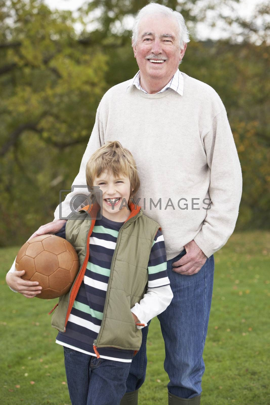 Grandfather With Grandson Holding Football Outside