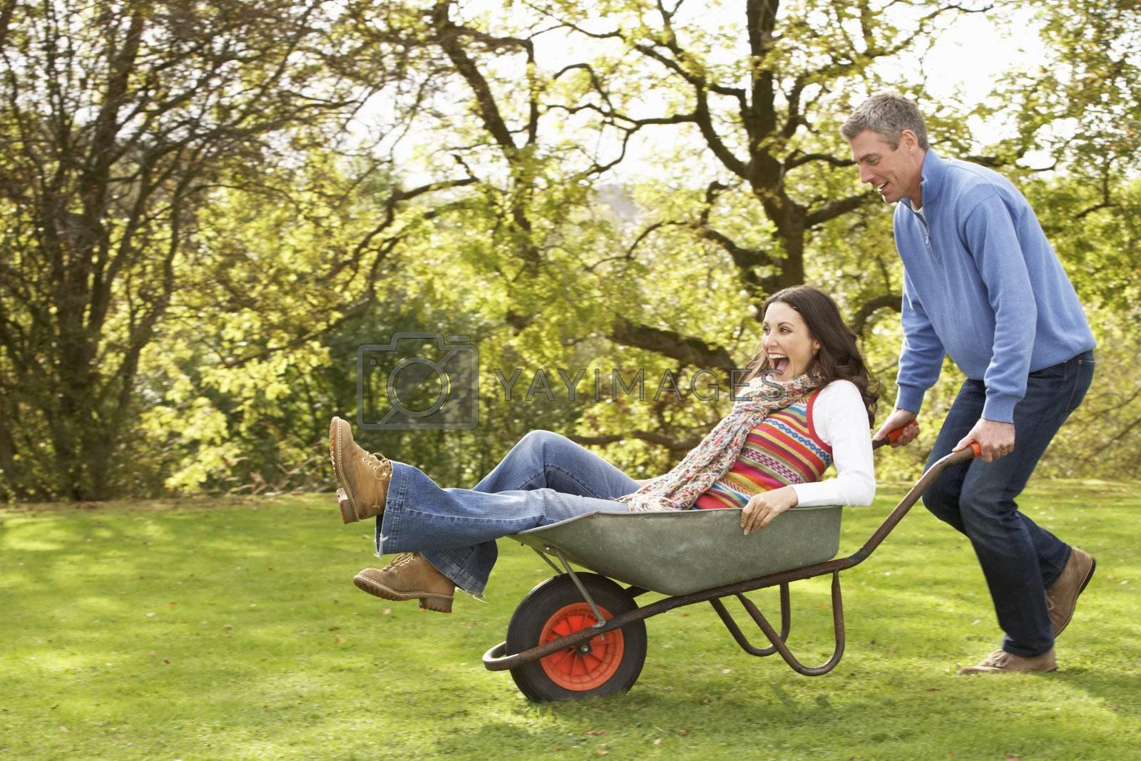 Couple With Man Giving Woman Ride In Wheelbarrow